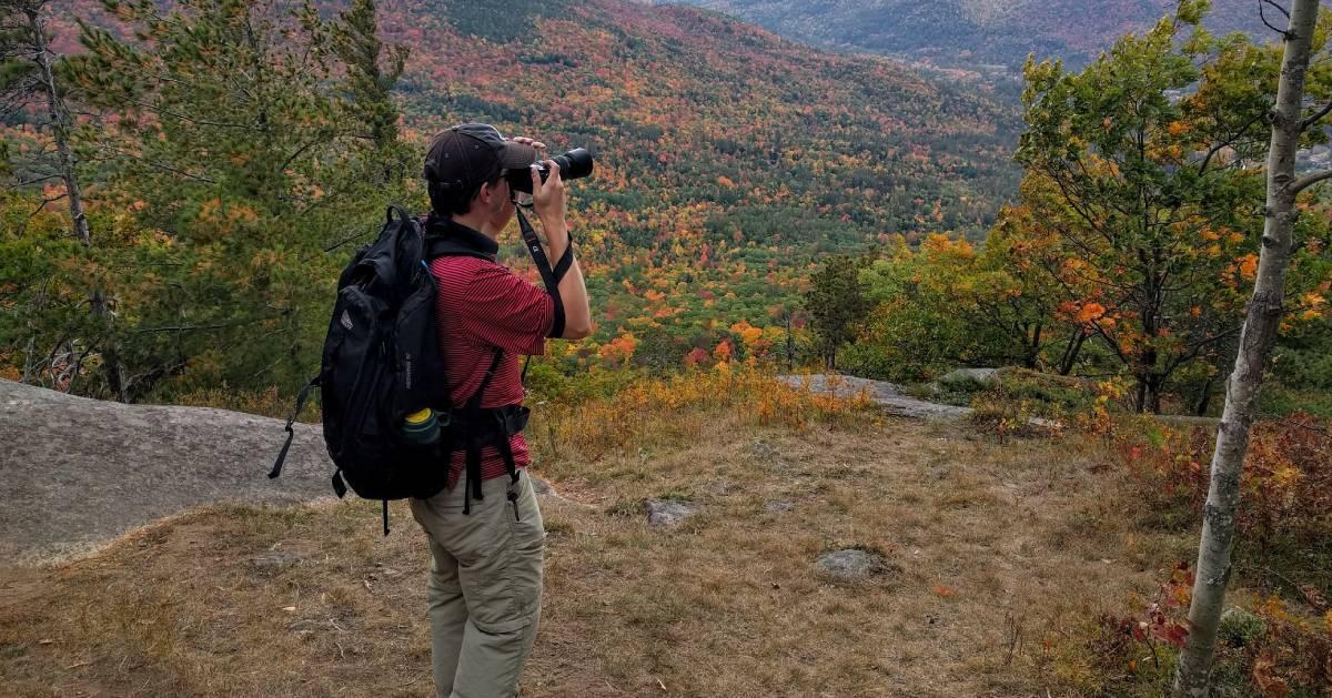 Man taking a photo during a hiking trip