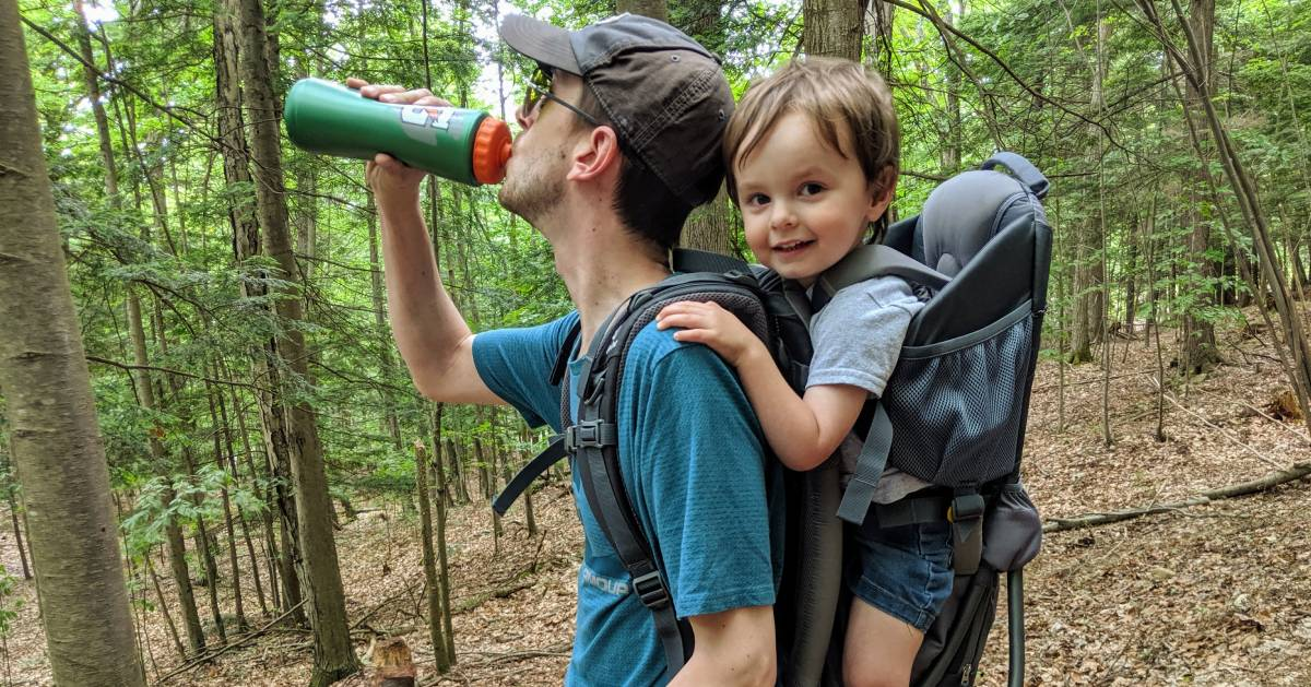 hiker with kid on back drinks water