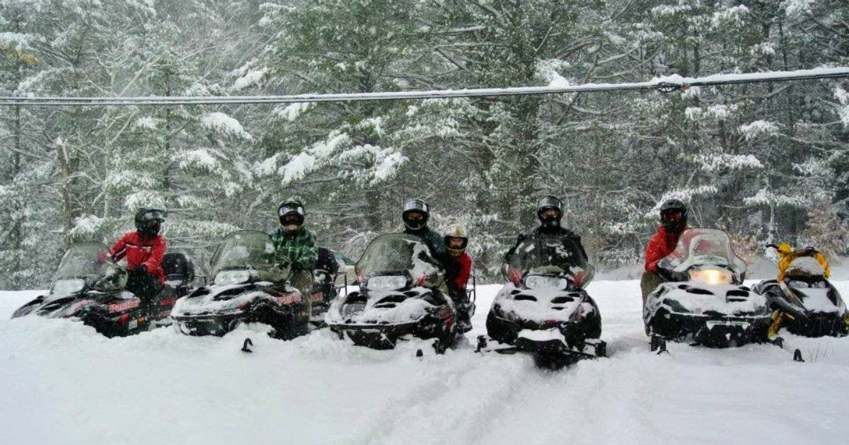 snowmobilers in a row in the snow
