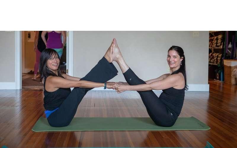 two women on a yoga mat posing