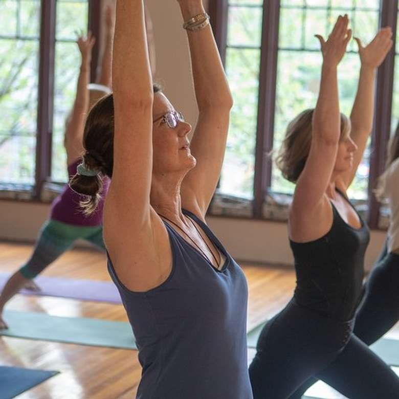 group of women performing a yoga pose in class