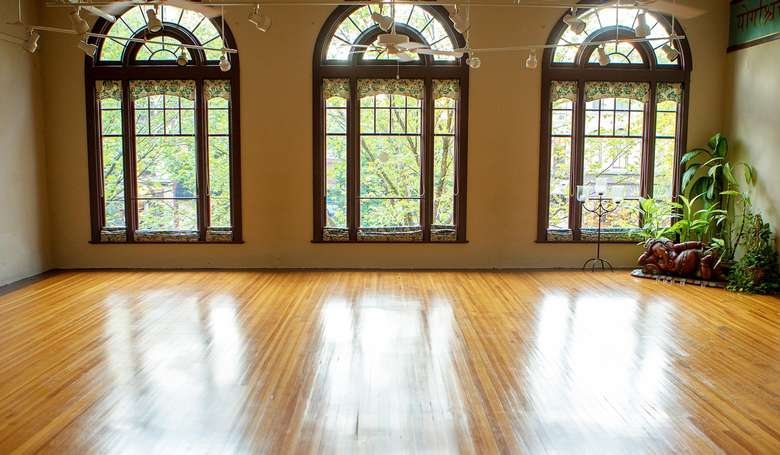 a spacious and sunny room with large windows