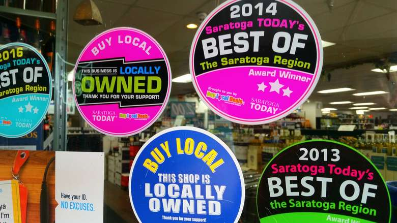 regional accolade stickers on the window of a store