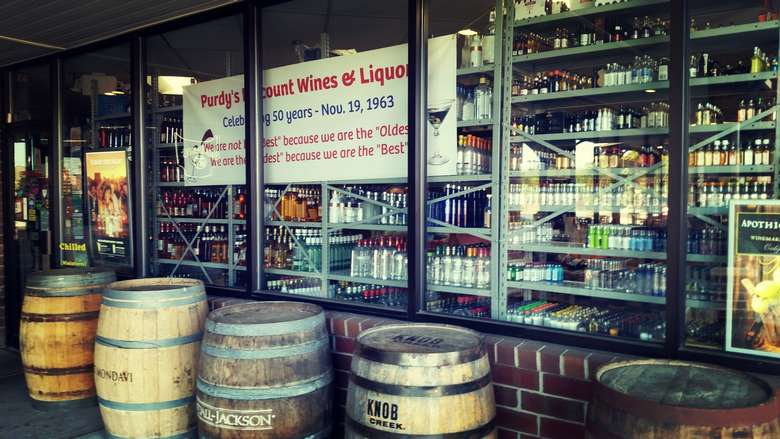 racks of wine seen inside a liquor store with large wine barrels outside of it