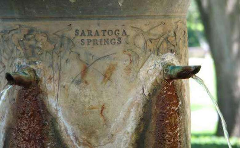 close-up view of congress spring shooting water into a basin with saratoga springs etched into the side of the spring