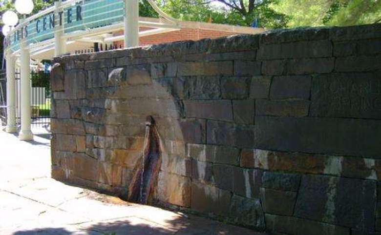 mineral spring jutting out of a stone wall with the saratoga performing arts center entrance visible to the side