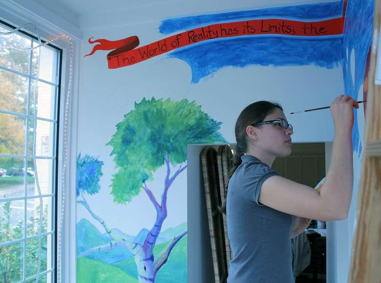 Artist Emily Thomson painting mural for LARAC's display case window