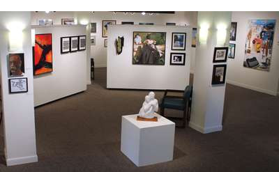 art gallery with sculptures and pictures hanging on the walls