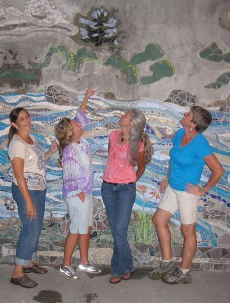 four women posing in front of a large mural