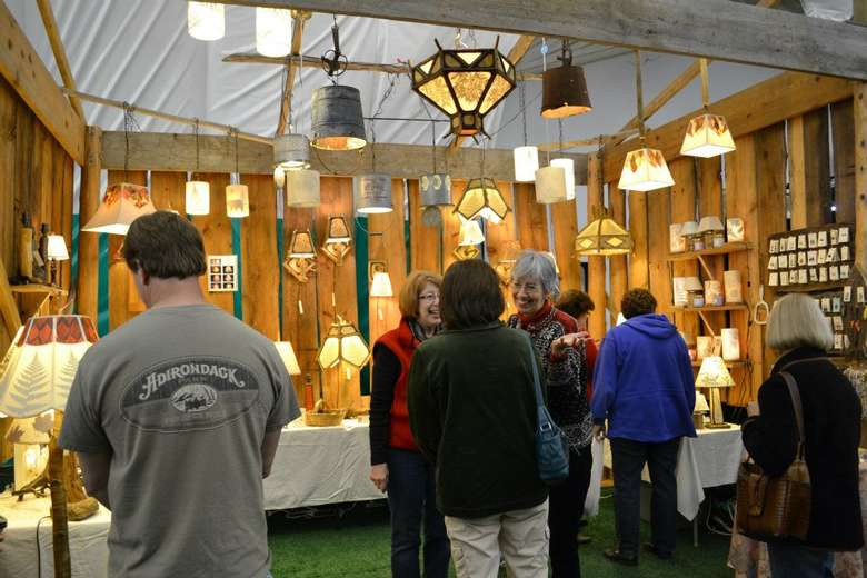 people browsing a light vendor booth at an indoor arts festival