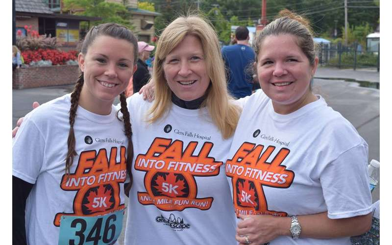 three women in Fall Into Fitness 5K shirts
