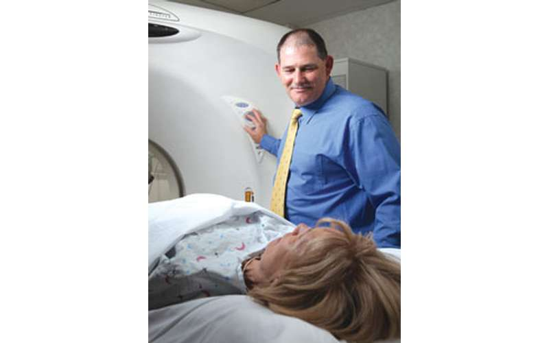 a man smiling at a woman as she's going into a CT scanner