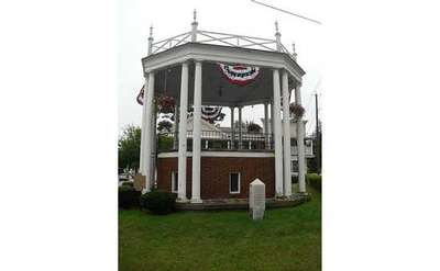 bandstand with red, white, and blue banners and green grass in front