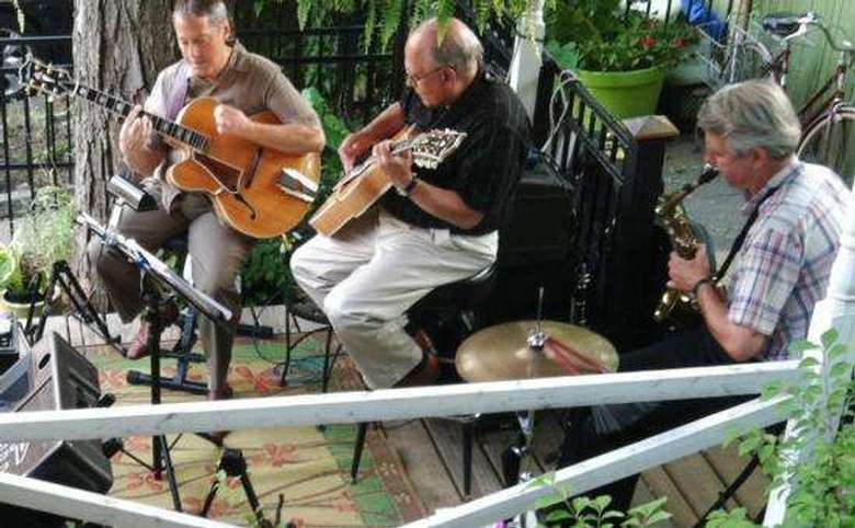 three musicians performing on an outdoor deck