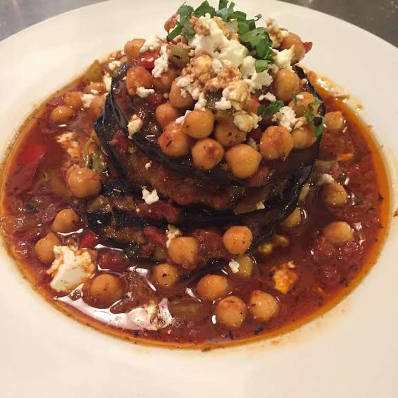 Grilled eggplant with sautéed chickpeas and roasted red peppers. Finished with local feta