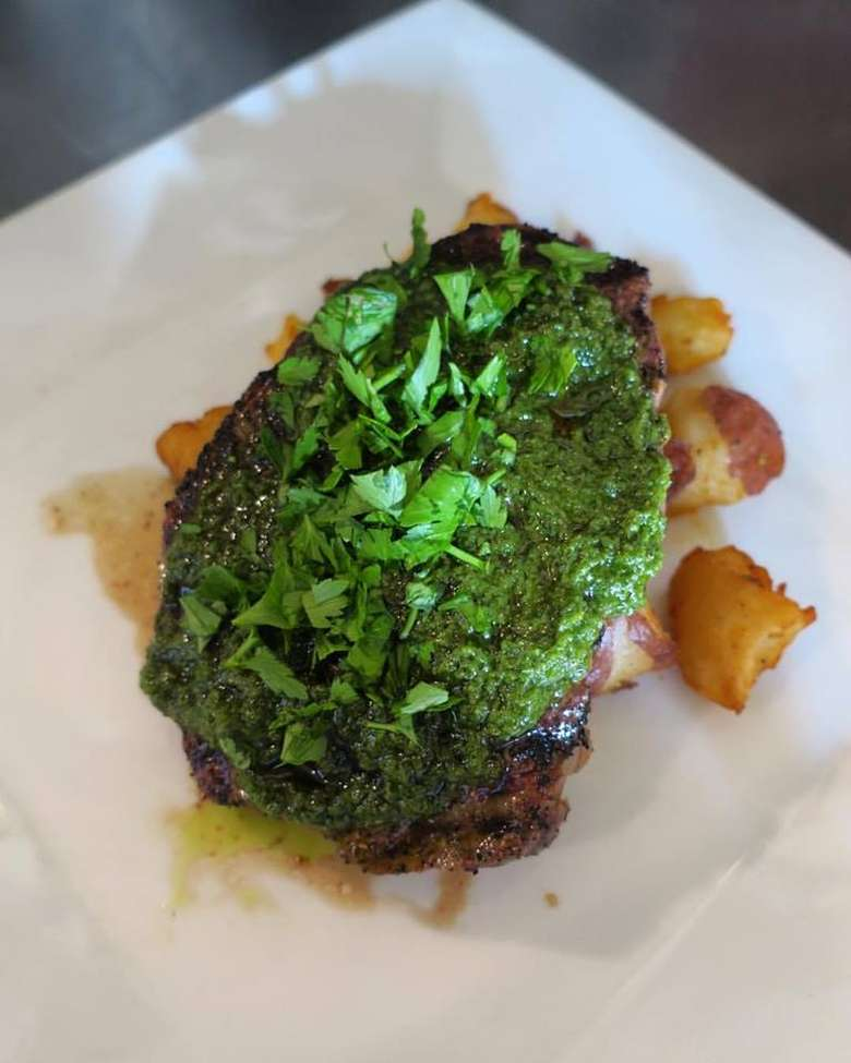 cut of meat with green sauce on top