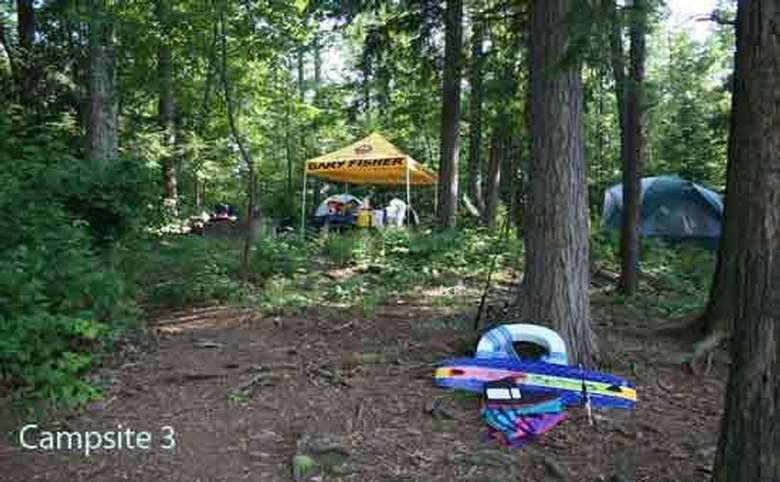 a tent in the woods with another tent area with just a yellow tarp roof