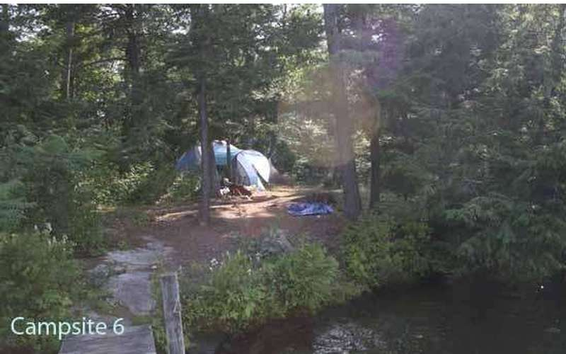 a tent set up just a short distance from a dock and shoreline