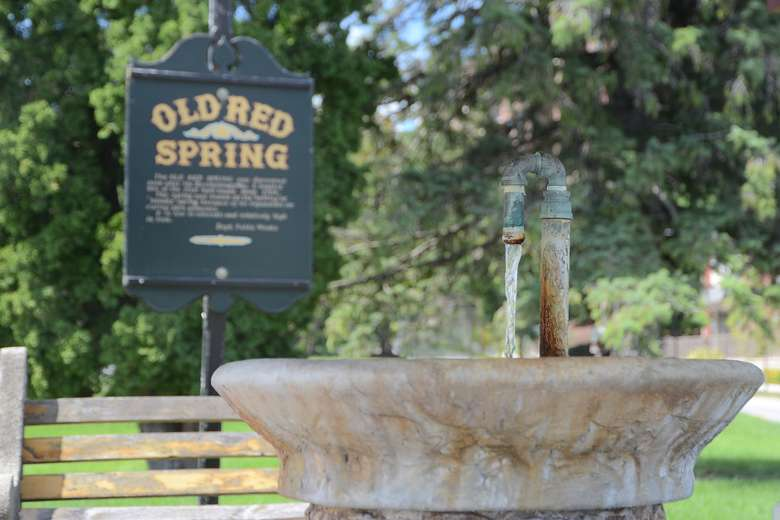 water flowing out of old red spring into its basin with an informational sign in the background