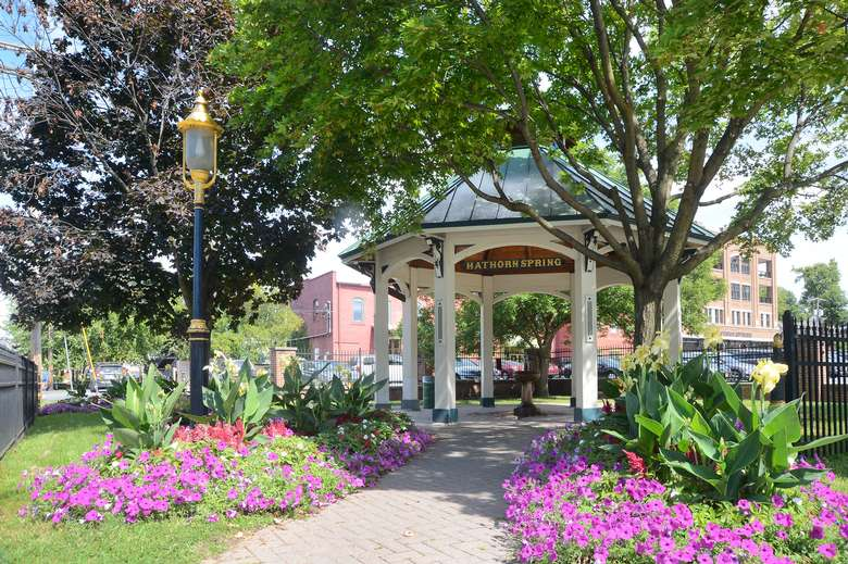 pavilion protecting hathorn spring one with lots of colorful flowers and trees surrounding it