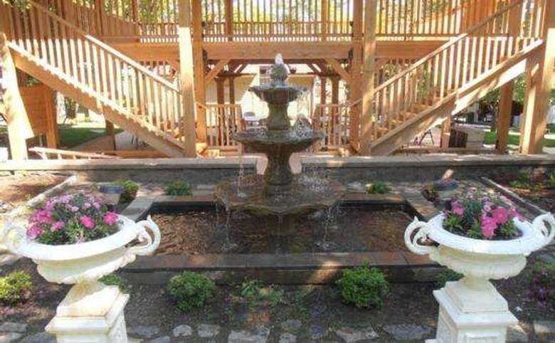fountain and flowers with a deck and two sets of stairs in the background
