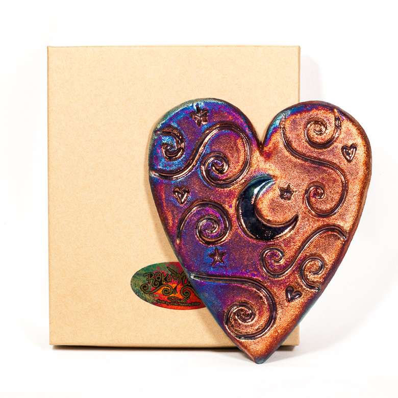 heart shaped figurine with a crescent moon cutout in front of a box