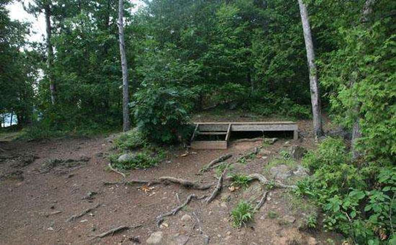 an outdoor wooden tent platform located on a small hill