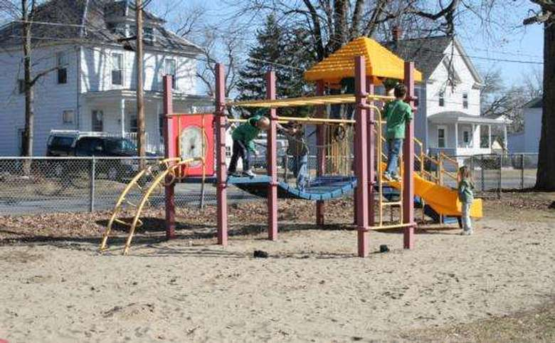 Playground on sand by road