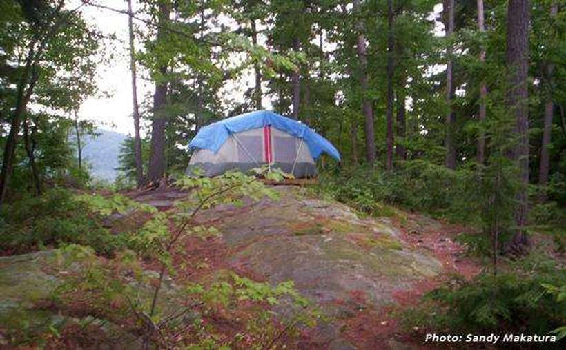 a large tent on top of a rocky surface in the woods