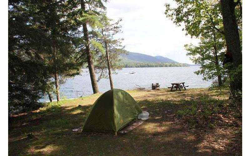a small green tent set up at a clear and flat campsite near a lake