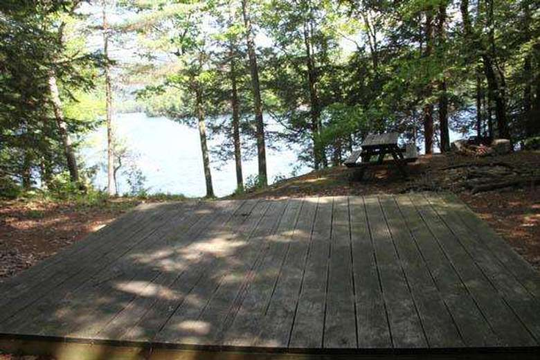 close up view of a wooden tent platform with a picnic table in the back