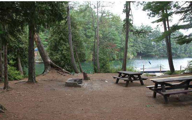 a large campsite with two picnic tables and a fire pit in the middle