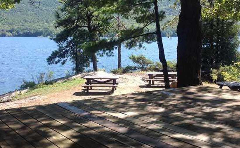 an island campsite with a couple picnic tables and a wooden spot for the tent