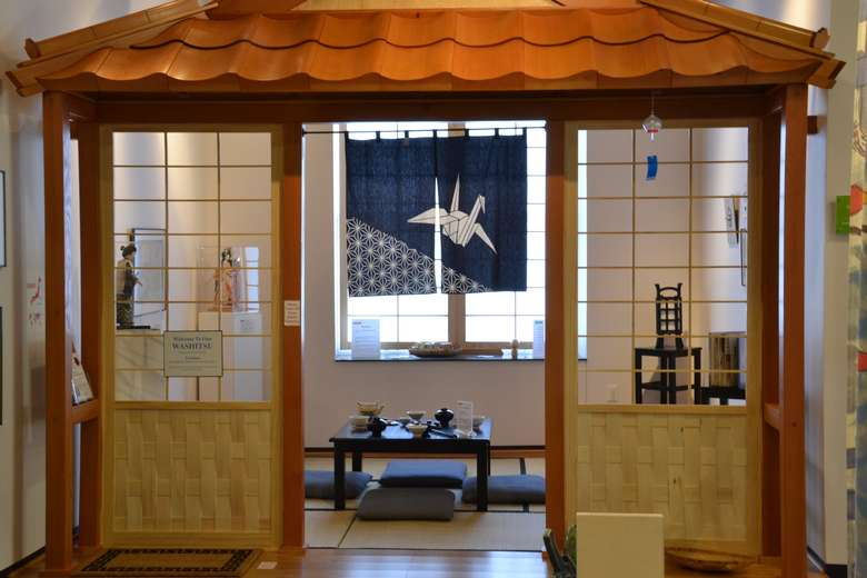 Japanese exhibit in a museum complete with low table, pillows for sitting, and more traditional decor