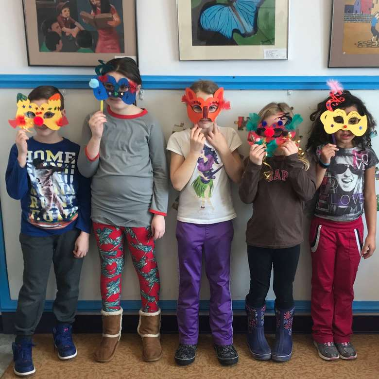 five kids holding homemade masks over their faces