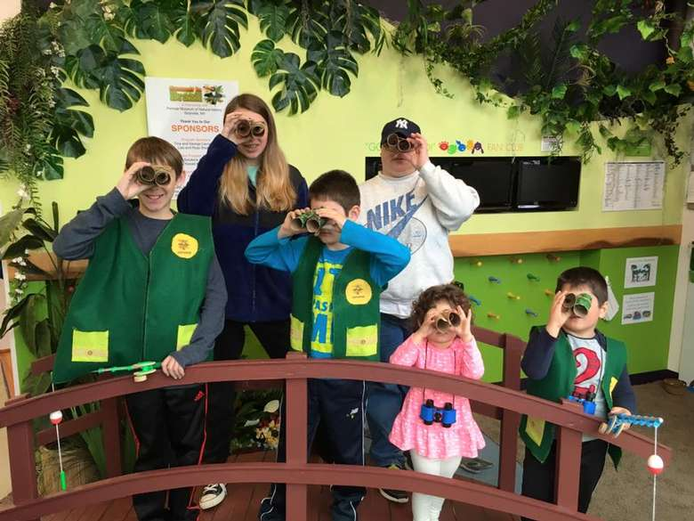 six kids looking through binoculars made out of toilet paper tubes