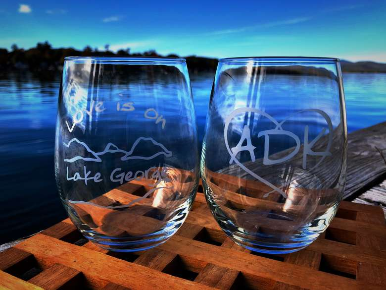 Two stemless wine glasses. One has Love is on Lake George text arched over and below a lake/mountain scene. The second glass has ADK in a heart.