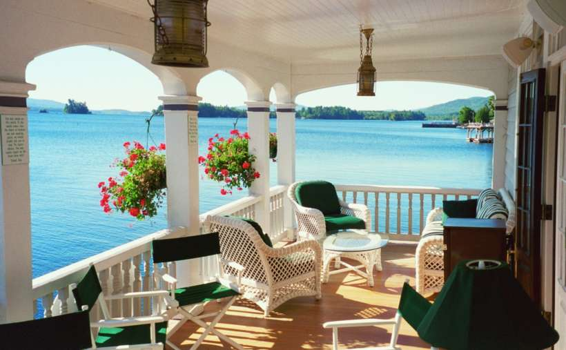a deck with white and green wicker chairs and a great view of the water