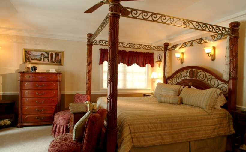 a large four poster wooden bed in a bedroom