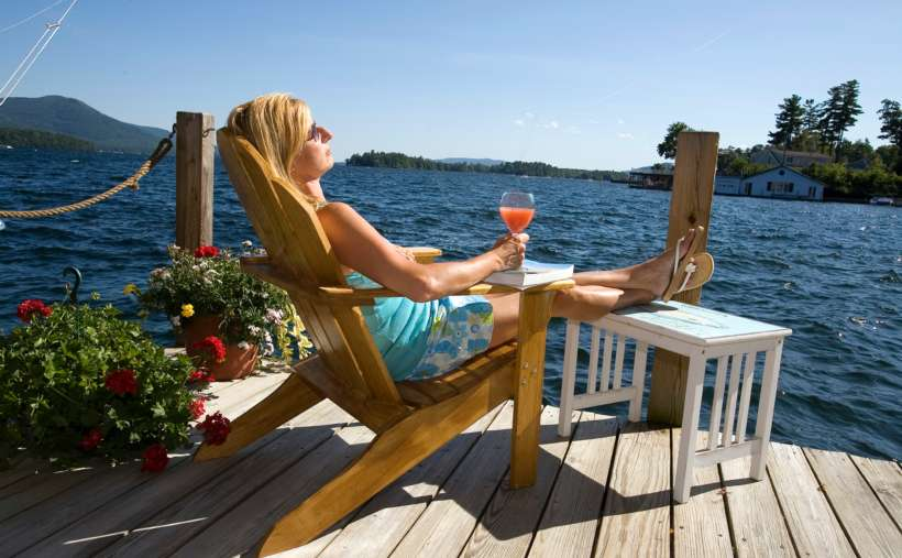 a woman relaxing with a cocktail on an Adirondack chair on a deck by water