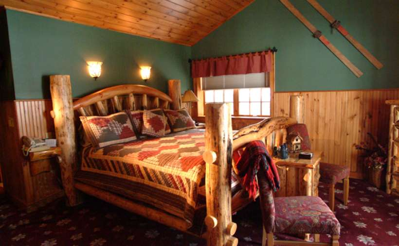 a wooden bed in a cabin-like bedroom