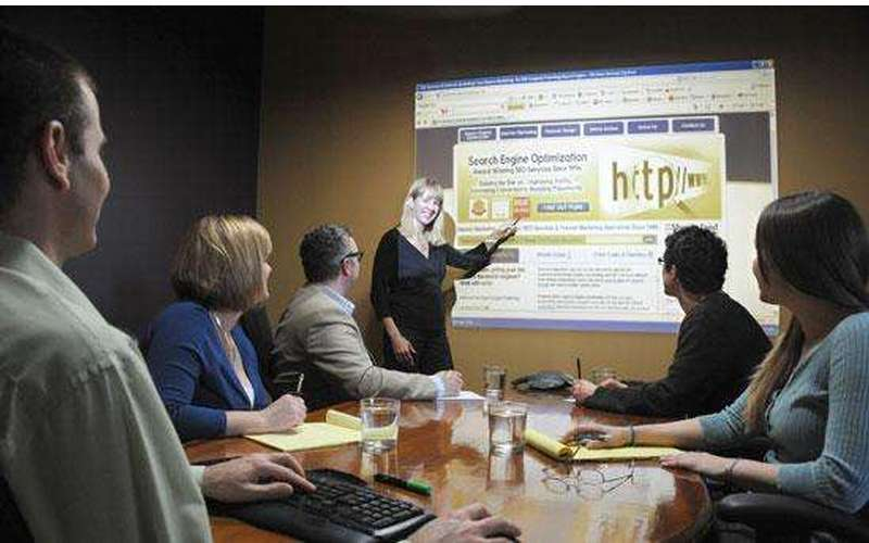 a woman speaking and pointing at a projector screen in a conference room
