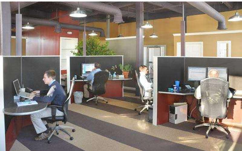 a large office space with workers at cubicles