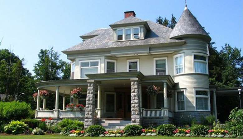 a Victorian-style bed and breakfast with wrap around porch