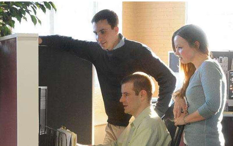 three people looking down at a computer screen