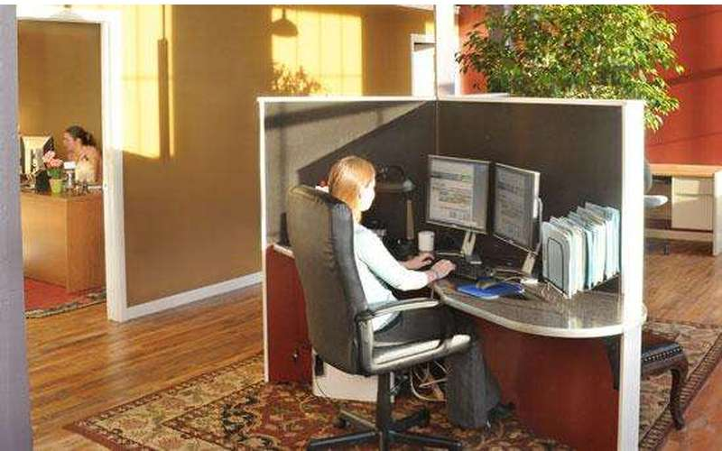 one person at a cubicle with a computer, and another person is seated in a side room