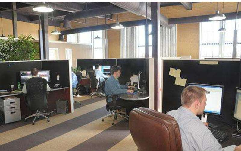 an office room with people at various cubicles
