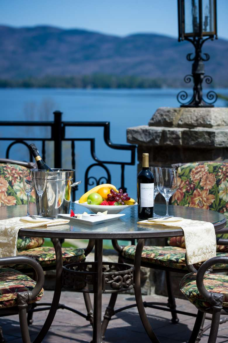 a fruit and wine spread on an outside table, water in the background