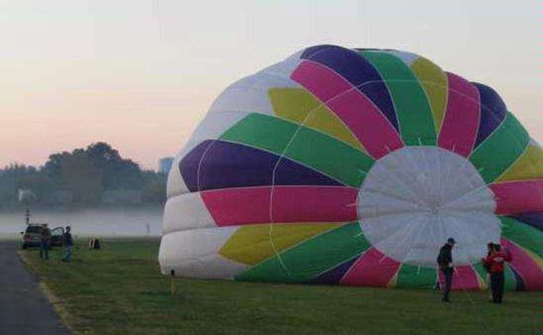 white, yellow, green, purple, and pink hot air balloon inflating in a field
