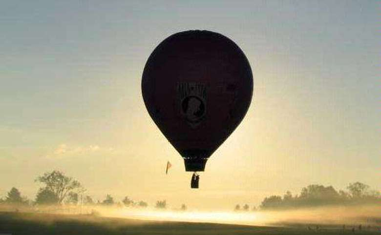 silhouette of a hot air balloon in flight at dawn